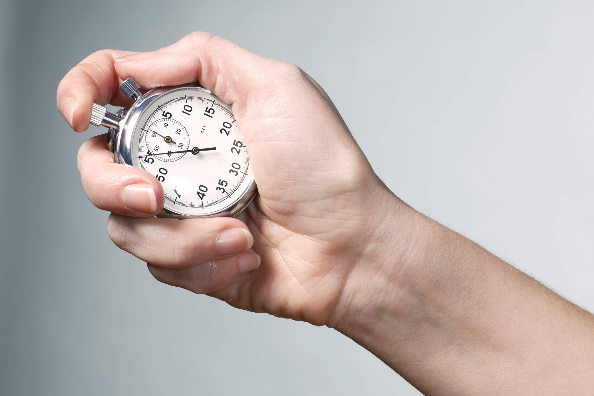 The picture shows a hand with a stopwatch.
