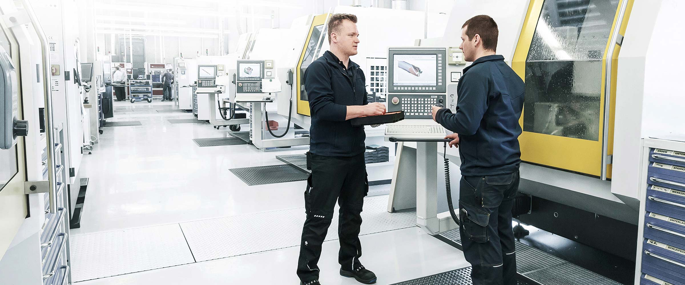 Two MAPAL employees are having a technical discussion in production.