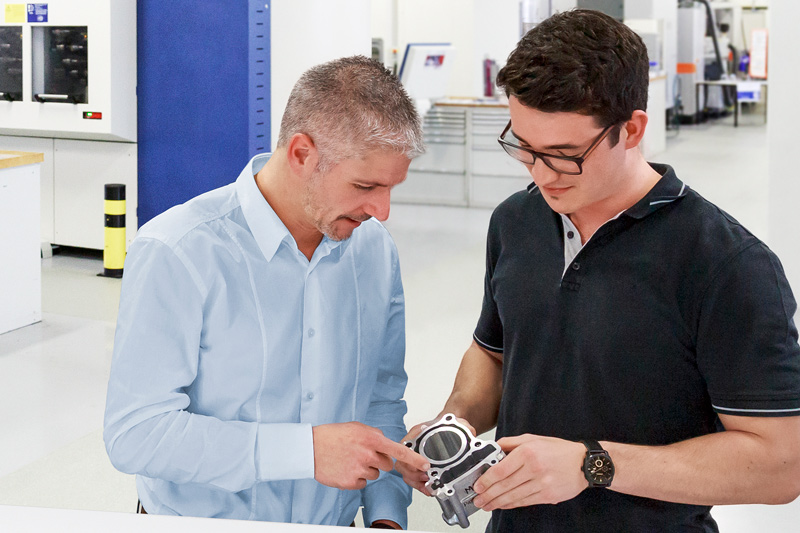 The picture shows two MAPAL employees who discuss a workpiece at the test centre in Aalen.